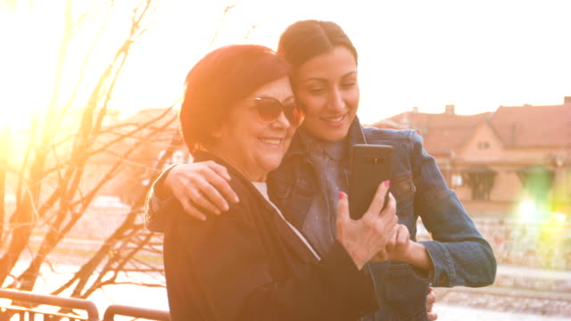 funny mother and daughter taking selfie - ventenne video stock e b–roll