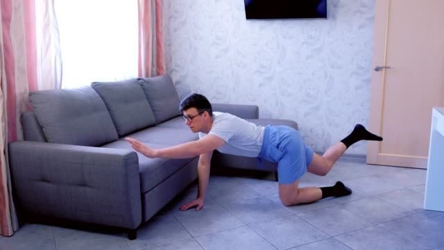Funny nerd man is doing balance pose on all fours at home and falling. Sport humor concept. video