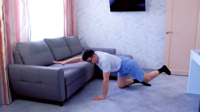 funny nerd man is doing balance pose on all fours at home. sport humor concept. - pantaloncini video stock e b–roll