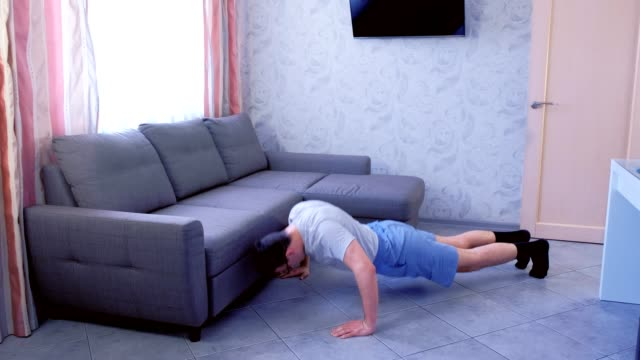 Funny nerd man is doing push-ups exercise laying on the floor at home. Sport humor concept. video