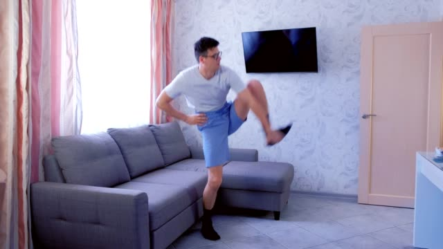Funny nerd man is doing stretching exercise for leg, trying to lift his leg up, and falling down the floor at home. Sport humor concept. video