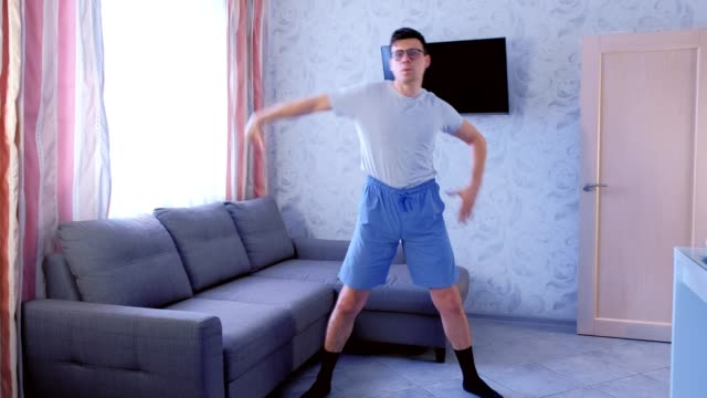 Funny nerd man is doing zumba aerobics exercises at home. Sport humor concept. video