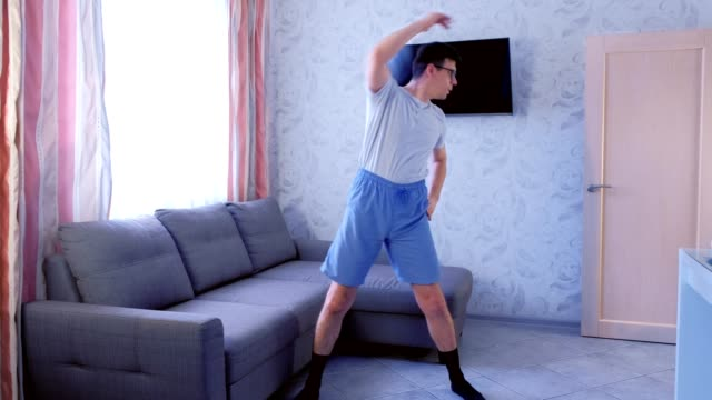 Funny nerd man is doing zumba exercises at home. Sport humor concept. video