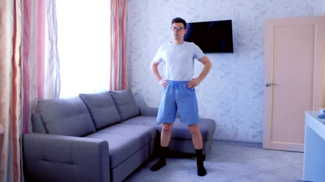 funny nerd man is making tilts to the sides exercise at home in living room. funny pulls up shorts during exercise. - szczupły filmów i materiałów b-roll