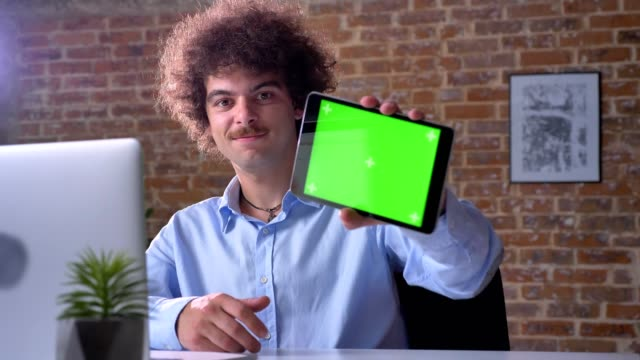 funny nerdy office worker with volume curly hair pointing tablet with chroma key at camera and smiling, man with mustache - mostrare video stock e b–roll