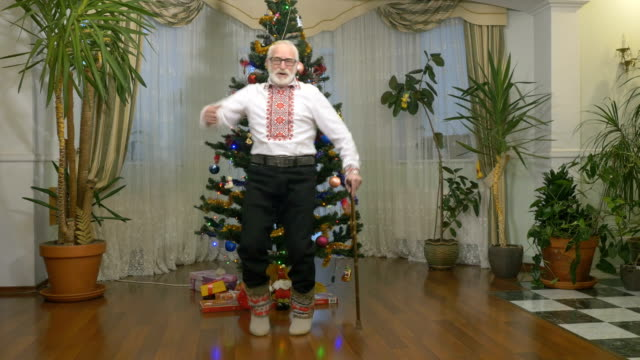 Funny old man dances near the Christmas tree video