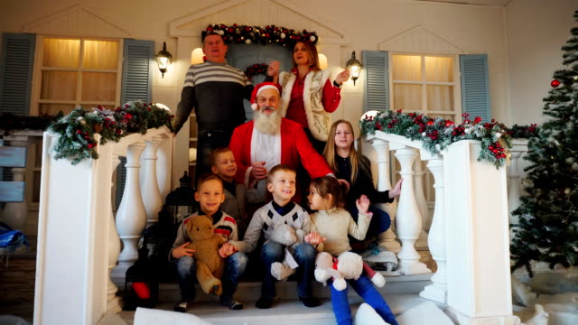 Funny parents, male female children and father Christmas sing songs, being on porch of beautifully decorated house video