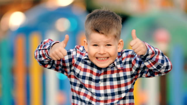funny positive little boy gesturing thumbs up on a colourful background - scolaro video stock e b–roll