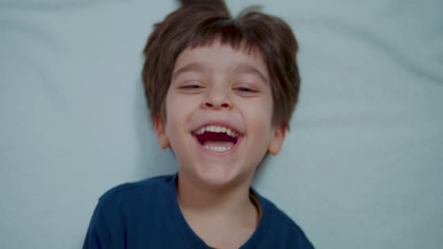 Funny positive little boy laughing and looking at camera. Happy child. video