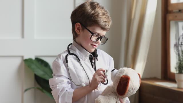 rolig förskolepojke pojke bära medicinsk päls hålla stetoskop lyssna leksak - veterinär, undersökning bildbanksvideor och videomaterial från bakom kulisserna