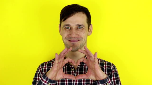 Funny, pretty guy smiling and folding a heart sign out of his hands. Portrait of a young guy, he smiles and shows a heart sign from his hands.