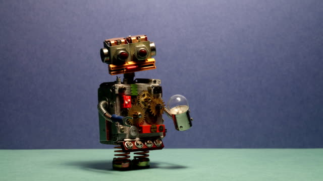 Funny robot serviceman walks and waving his arms. Funny toy cyborg with light bulb. Blue wall green floor background video