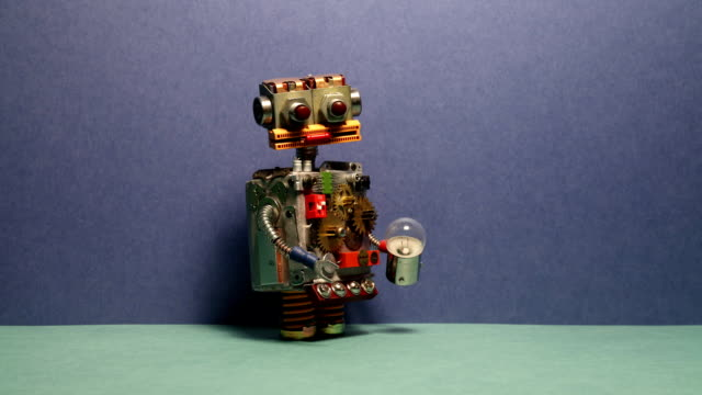 Funny robot serviceman walks and waving his arms. Toy cyborg with light bulb. Blue wall green floor background video