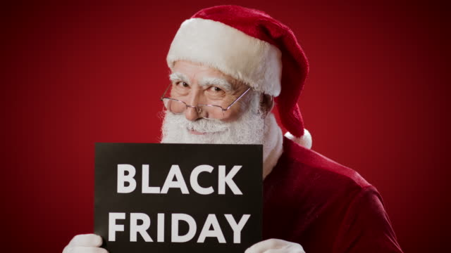 funny santa claus holding black friday lettering in hands - black friday стоковые видео и кадры b-roll