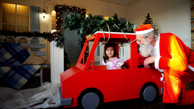 Funny Santa Claus playing with little princes waving hand in red car video