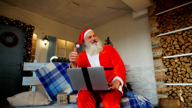 Funny Santa Claus showing thumbs up and working with laptop video