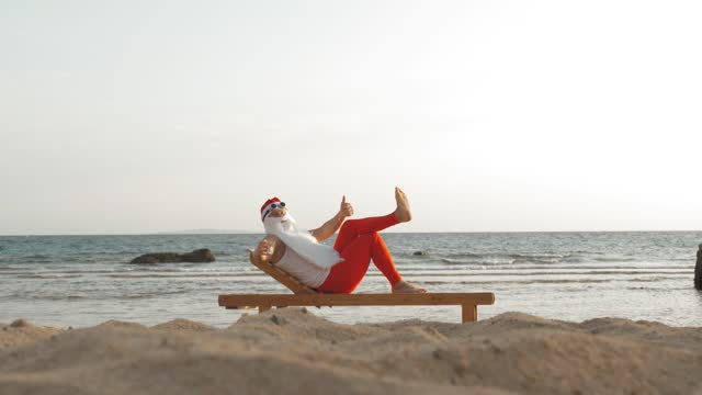 funny santa claus sunbathes. santa lies on wooden lounger on beach by the sea and drinks a delicious cocktail. santa claus is on summer vacation, at the seashore video