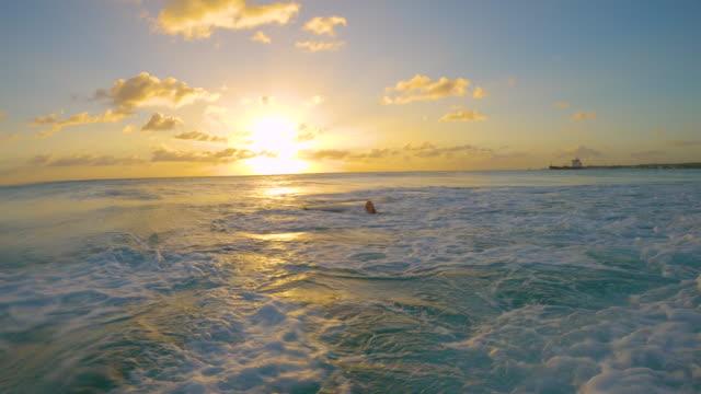 vídeos de stock, filmes e b-roll de slow motion: tiro engraçado de uma mulher aprendendo a surfar caindo em água turquesa - azul turquesa