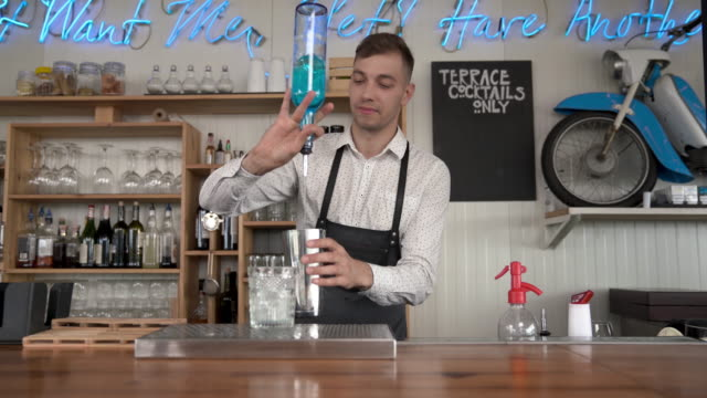 Funny, smiling bartender pours a blue curacao liquor into a glass with ice cubes. Flair bartending. video