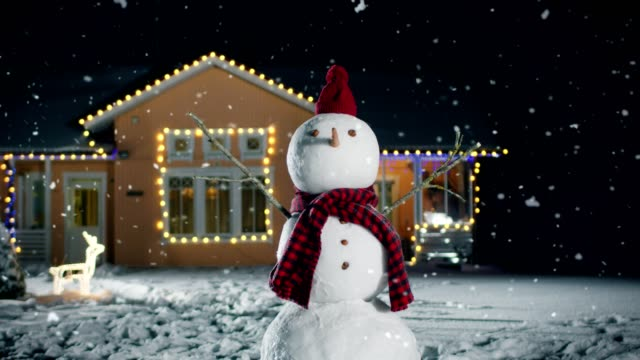 Funny Snowman Wearing Hat and Scarf Standing in the Backyard of the Idyllic House Decorated with Garlands on Christmas Eve. Soft Snow is Falling on that Magical Winter Evening. Funny Snowman Wearing Hat and Scarf Standing in the Backyard of the Idyllic House Decorated with Garlands on Christmas Eve. Soft Snow is Falling on that Magical Winter Evening. Shot on RED EPIC-W 8K Helium Cinema Camera. snowman stock videos & royalty-free footage