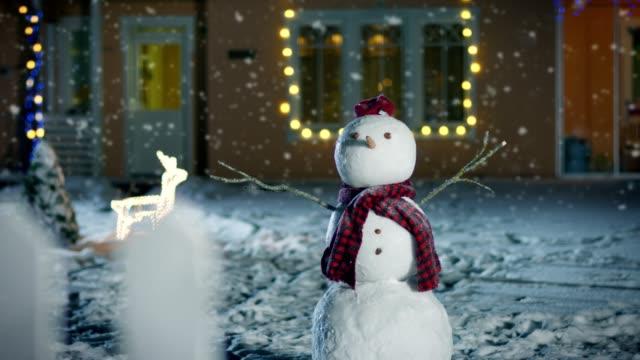 lustiger schneemann mit hut und schal steht im hinterhof des hauses idyllisch am heiligabend mit girlanden geschmückt. weichen schnee fällt an diesem magischen winterabend. - karotte peace stock-videos und b-roll-filmmaterial