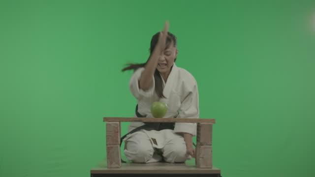 funny sports yong woman, eli ile apple'ı parçalamaktır. - karate stok videoları ve detay görüntü çekimi