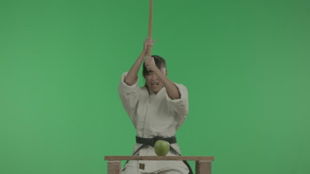 lustige sport junge frau ist zerschlagen apple mit stick. - menschliche erzeugnisse stock-videos und b-roll-filmmaterial