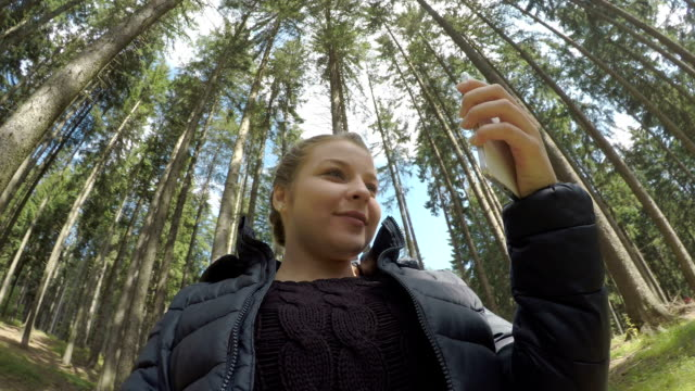 funny teen girl taking selfies with smartphone in a forest resting after mountain hiking 360 view of wood in background - ritratto 360 gradi video stock e b–roll
