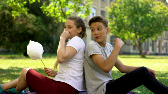 Funny teens sitting back to back and fooling around while eating cotton candy Funny teens sitting back to back and fooling around while eating cotton candy back to back stock videos & royalty-free footage