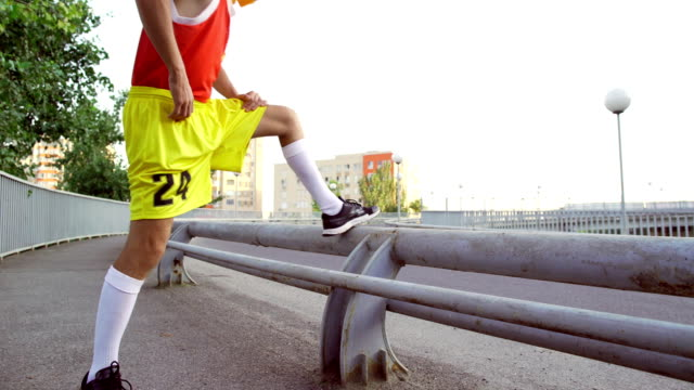 A funny, thin man makes a warm-up before jogging video