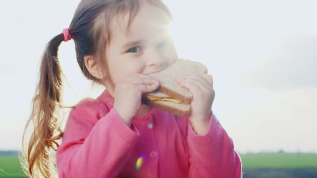 vídeos de stock e filmes b-roll de funny three years girl, eating a sandwich in the sun - sanduíche