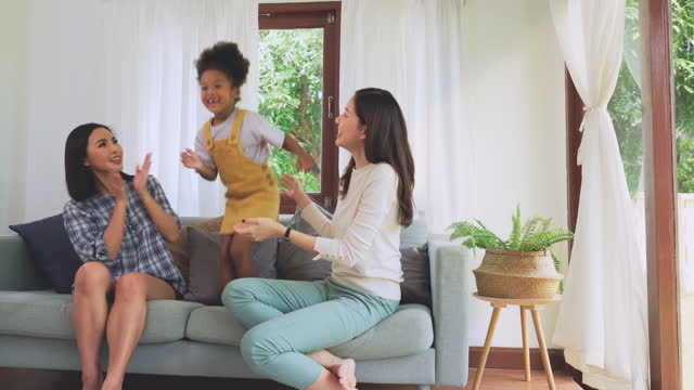 funny time!  Adopted African daughter stand to dancing with Asian LGBTQ  family on sofa, woman couple adopts teenager girls as modern family spending weekend time together, having to smile with toothless, feeling happy, positive emotion together in home.