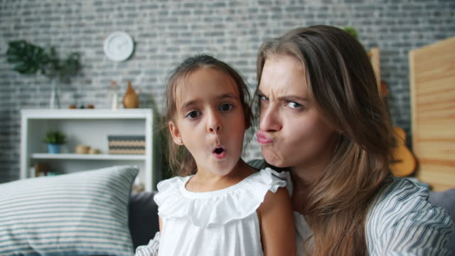 POV of funny woman and girl mother and daughter making funny faces taking selfie