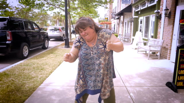 A funny woman dancing and pumping her arms in the air on a city sidewalk A heavy beautiful woman swaying, dancing, and pumping her arms in the air in slow motion on a sidewalk outside in a commercial shopping center plus size model stock videos & royalty-free footage