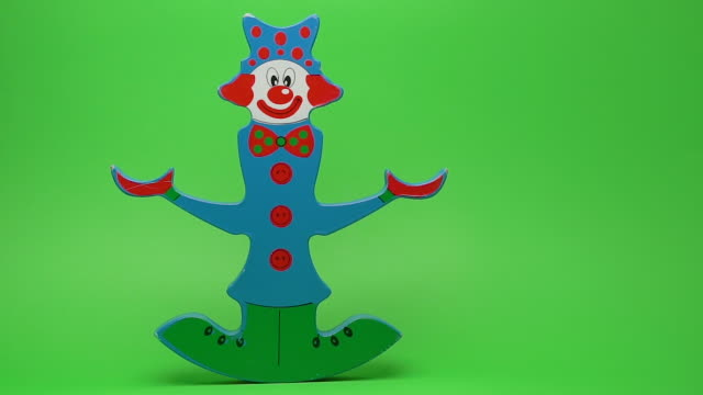 Funny wooden clown on green background