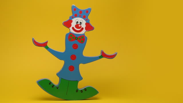 Funny wooden clown on yellow background