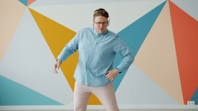 funny young man in wireless headphones dancing indoors on colorful background - kolor tła filmów i materiałów b-roll