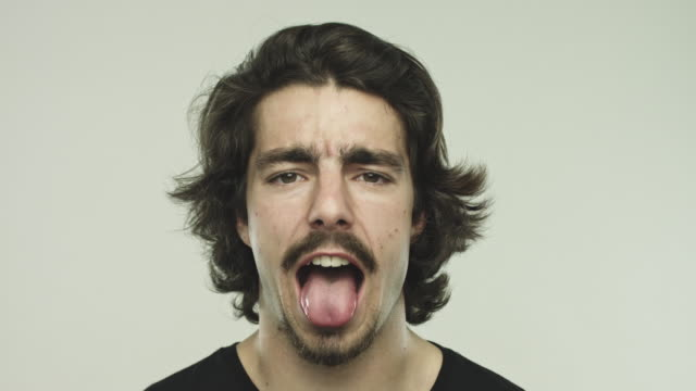 funny young man sticking out his tongue - lingua bocca video stock e b–roll