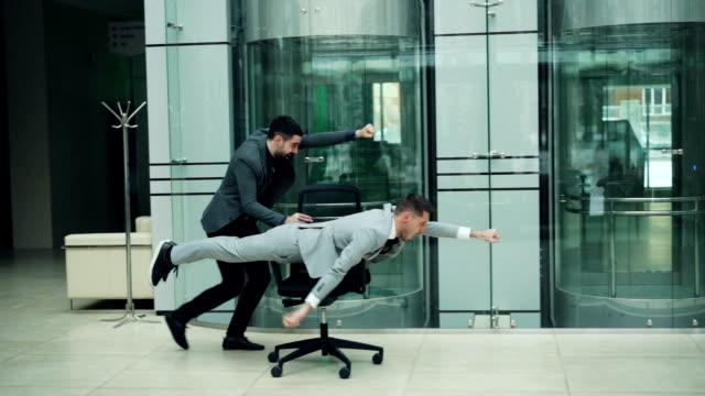 lustige junge männer haben spaß mit rollenden stuhl, man treibt sessel anderen drin liegt und in büro halle voran. jugend und freude konzept. - bizarr stock-videos und b-roll-filmmaterial
