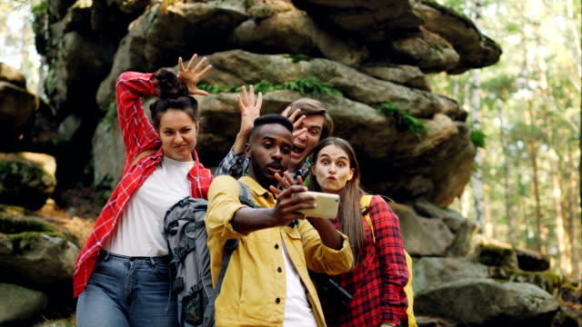 funny young people happy friends are taking selfie in wood with mossy rocks in background, african american guy is holding smartphone, men and women are posing. - trekking video stock e b–roll