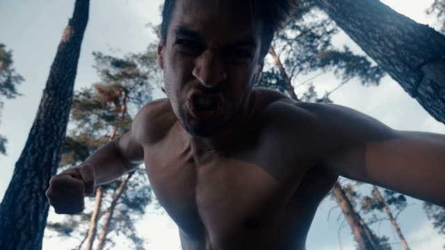 furious aggressive man beats with his fists the lying person outdoor at forest - pugno video stock e b–roll