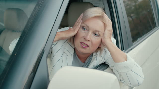 Furious blond woman nervously scolding drivers on road, city traffic jam, stress