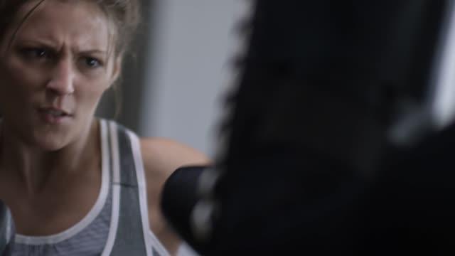 vídeos de stock e filmes b-roll de furious woman exercising in gym - boxe tailandês