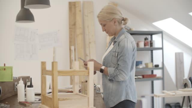 4K: Furniture Designer Using Smart Phone In Her Workshop. video