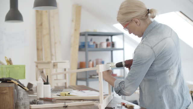 4K: Furniture Designer Working On New Project In Her Workshop. Mature Female furniture designer attaching model she projected. She is using cordless screwdriver and attaching wooden elements. Shot with Sony FS700R w/Odyssey7Q Native ProRes422HQ no conversion. cordless phone stock videos & royalty-free footage