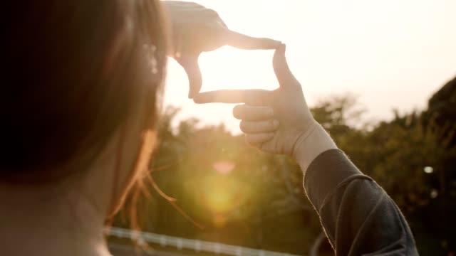 framtida planering, närbild av kvinnan händer gör ram gest med sol uppgång, kvinna fånga sol uppgången, solljus utomhus. - föreställningsförmåga bildbanksvideor och videomaterial från bakom kulisserna