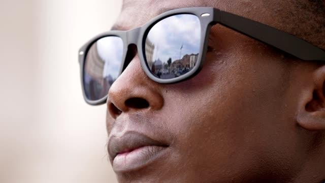 zukunft, erfolg, jugend. junger schwarzer mann sieht seine sonnenbrille abnehmen - sonnenbrille stock-videos und b-roll-filmmaterial