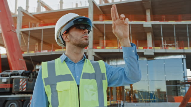 Futuristic Architectural Engineer Wearing Augmented Reality Headset and Using Gestures to Control Commercial / Industrial Building Construction Site. In the Background Skyscraper Formwork Frames and Industrial Crane