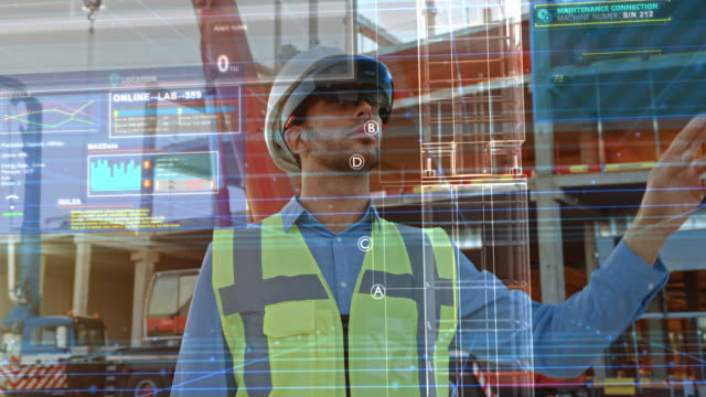 Futuristic Architectural Engineer Wearing Augmented Reality Headset, Uses Gestures to Create 3D Graphics VFX Model of a Building with Infographics. In Background Construction Site in Progress Futuristic Architectural Engineer Wearing Augmented Reality Headset, Uses Gestures to Create 3D Graphics VFX Model of a Building with Infographics. In Background Construction Site in Progress futuristic architecture stock videos & royalty-free footage