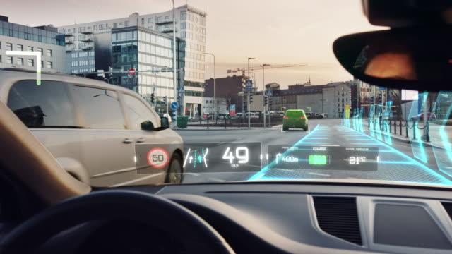 都市を移動する未来的な自律型自動運転車、インフォグラフィックスを示すヘッドアップディスプレイhud:スピード、距離、ナビゲーション。道路スキャン。ドライバーシート視点ビューpov/� - 自動化点の映像素材/bロール